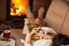 Woman enjoying the fire and some fine company - her kitten Royalty Free Stock Photo