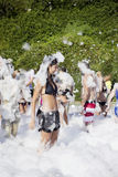Woman  enjoying  a foam party on the beach. Foam Party on the beach Stock Photography
