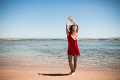 Woman enjoying freedom on a ocean shore with hands raised on water background. Summer vocation. Royalty Free Stock Photo