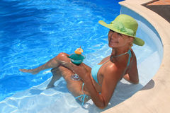 Woman enjoying a fresh cocktail in a blue pool Royalty Free Stock Photography