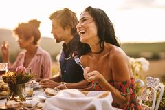 Woman enjoying with friends at outdoor dinner party. Laughing talking with friends while having food at a party outdoors. Woman enjoying with friends at a dinner stock images