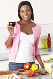 Woman Enjoying Glass Of Wine In Kitchen Royalty Free Stock Photos