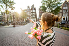 Woman with tulips in Amsterdam city. Woman enjoying great view on the buildings holding a bouquet of pink tulips in Amsterdam city Royalty Free Stock Images