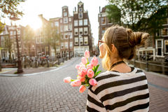 Woman with tulips in Amsterdam city. Woman enjoying great view on the buildings holding a bouquet of pink tulips in Amsterdam city Royalty Free Stock Photography