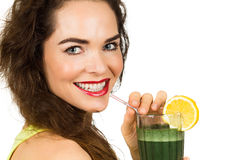 Woman enjoying a green smoothie. Close-up portrait of a beautiful healthy woman drinking an organic green smoothie. Isolated on white stock photos