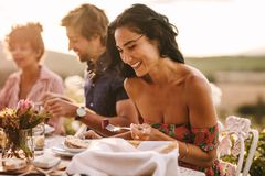 Woman enjoying having food with friends at a party. Beautiful women eating food sitting with friends at a party outdoors. Woman enjoying having food with friends stock images