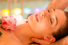 Woman enjoying head massage in a spa. With chromatherapy or color therapy royalty free stock photos