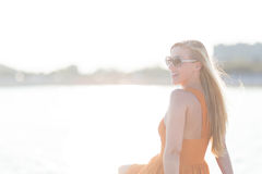 Woman enjoying the heat of the summer sun. Sitting at the seaside in a summer dress and sunglasses, high key portrait with flare effect Stock Image