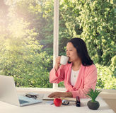 Woman enjoying her coffee in the morning light while working fro Royalty Free Stock Photo