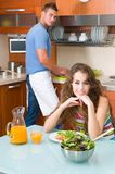 Woman enjoying her salad and man washing Stock Images