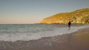 Woman enjoying her summer vacation at Zorkos beach in Andros playing with the waves. stock footage