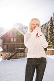 Woman enjoying hot beverage while standing near mountain house. Christmas season in relaxed style of contemporary countryside living. Happy young woman in white Stock Photo