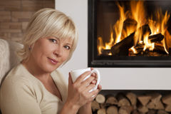 Woman enjoying hot drink near home fireplace Royalty Free Stock Photo