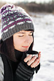 Woman enjoying hot tea outdoors in winter. Portrait of the beautiful girl drinking hot tea in snowy winter Stock Images
