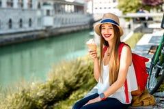Woman enjoying ice cream in Ljubljana city. Young female tourist enjoying ice cream sitting near the water chanal in Ljubljana city center. Traveling in Slovenia royalty free stock photo