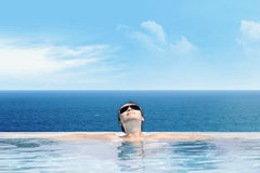 Woman enjoying infinity pool Stock Images