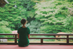 Woman enjoying Japanese garden from a temple terrace, Kyoto, Japan Stock Image
