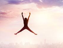 Woman enjoying jumping while chilling out on city and sky Stock Images