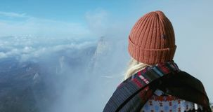 Woman enjoying landscape in mountains over clouds Travel Lifestyle concept. Adventure vacations outdoor happy emotions girl wearing winter clothing knit hat stock video