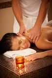 Woman enjoying massage. Young woman enjoying massage with eyes closed in wellness environment Royalty Free Stock Photo