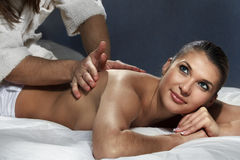 Woman enjoying a massage. Beautiful woman enjoying a massage on bed Stock Photography