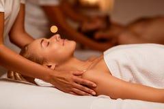 Woman Enjoying Massage During Couples Beauty Treatment Lying At Spa