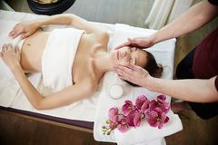 Woman Enjoying Massage in SPA. High angle portrait of young women enjoying face lifting massage lying on table in SPA center and relaxing, smiling blissfully Royalty Free Stock Images