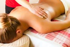 Woman enjoying massage in wellness spa Stock Image