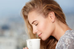 Woman enjoying morning coffee. Closeup portrait of a beautiful woman with closed eyes enjoying aroma of morning coffee, taking breakfast in outdoor cafe royalty free stock photos