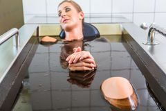 Woman enjoying mud bath alternative therapy. Woman having mud bath alternative therapy royalty free stock photo