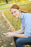 Woman Enjoying Music in a City Park Royalty Free Stock Image