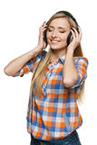 Woman enjoying music with closed eyes. Young female enjoying the music in headphones with closed eyes, isolated on white Stock Images