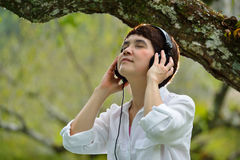 Woman enjoying music with headphones. Middle age woman enjoying music with headphones outdoors Royalty Free Stock Images