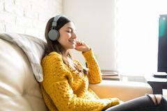 Woman Enjoying Music On Wireless Headphones. Side view of content woman listening to music on headphones at home royalty free stock photos