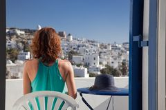 woman enjoying mykonos town view from terrace, Greece - summer holiday stock images
