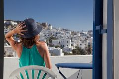 woman enjoying mykonos town view from terrace, Greece - summer holiday royalty free stock photo