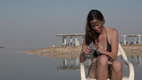 Woman enjoying the natural mineral mud sourced from the Dead Sea Israel stock video footage