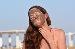 Woman enjoying the natural mineral mud sourced from the Dead Sea Royalty Free Stock Photos