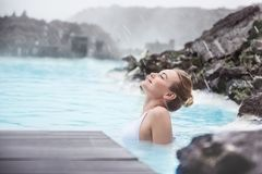 Woman enjoying blue lagoon. Woman enjoying natural spa, Blue Lagoon is a geothermal spa in southwestern Iceland, is located in a lava field near Grindavk on the stock images