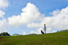 Woman enjoying the nature. On blue sky background with dog beside her Royalty Free Stock Photos
