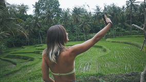 Young woman enjoying the nature in green tropical forest and make selfie with smartphone. Woman enjoying the nature in green tropical forest and make selfie with stock footage