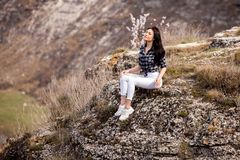 A young traveler girl sit on the top of valley. Young girl love wild life, travel, freedom. Woman Enjoying Nature. Travel and wanderlust concept stock photos