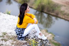 A young traveler girl sit on the top of valley. Young girl love wild life, travel, freedom. Woman Enjoying Nature. Travel and wanderlust concept royalty free stock image