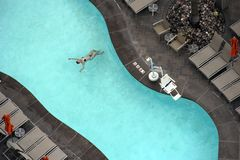 Woman enjoying an outdoor pool. Woman floating in an outdoor swimming pool stock image