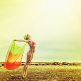 Woman enjoying the outdoors in the sun . Beautiful girl in a bikini on the beach spreading pareo in hands reaching for the sun royalty free stock photo