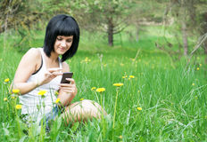 Woman enjoying the outdoors using her cell phone Stock Image