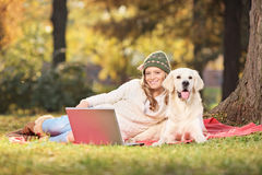 Woman enjoying a picnic with her dog in park Royalty Free Stock Image
