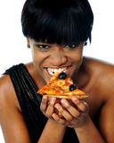 Woman enjoying pie of a pizza Royalty Free Stock Images