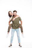 Woman enjoying piggyback ride. Brunette young women enjoying piggyback ride on her men and touching his face Royalty Free Stock Photography
