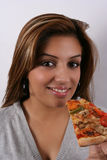 Woman enjoying pizza. A studio portrait of a beautiful Asian woman with friendly smiling facial expression eating a slice of pizza royalty free stock images